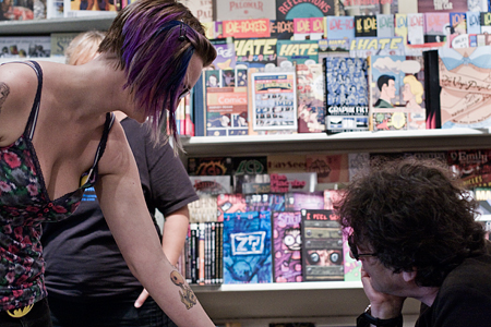 A fan shows Neil her tattoo of his baby gargoyle character Goldie, just prior to getting him to sign her arm. Immediately afterwards, she would have his signature tattooed on. Seth Rosenblatt (c) 2009.