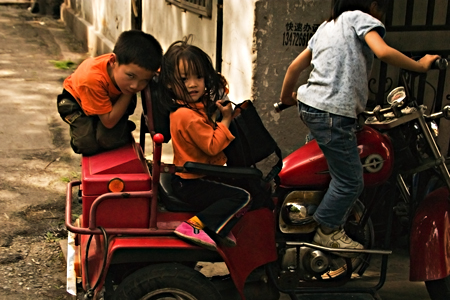 Kids on a motorized tricycle, near Old Town, Shanghai, China. Seth Rosenblatt (c) 2006.