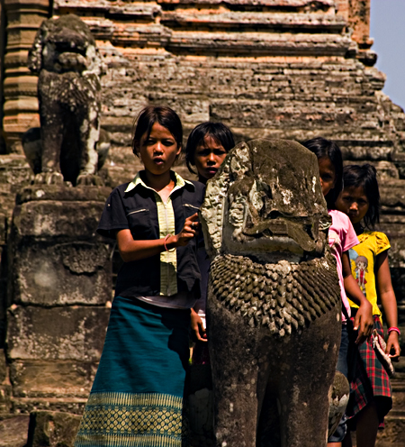 Vendor girls hide behind a lion at the top of East Mebon, Angkor Wat, Cambodia. Seth Rosenblatt (c) 2006.