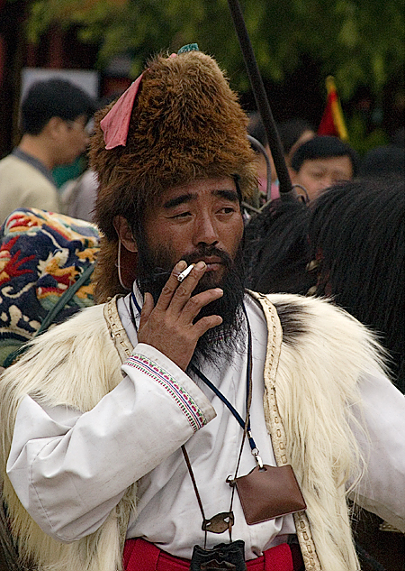 An actor in a Tibetan foothills costume takes a break, Old Town, Lijiang, Yunnan Province, China. Seth Rosenblatt (c) 2006.