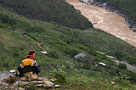 A Naxi woman watches the Yangzi River in Tiger Leaping Gorge, Yunnan Province, China. Seth Rosenblatt (c) 2006.
