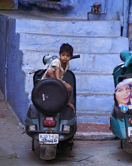 Young girl playing on moped, Udaipur, Rajasthan, India. Seth Rosenblatt (c) 2006.